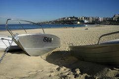 Boats on a beach. Coogee beach in Sydney; three boats in foreground anchored in sand; too cold to swim Royalty Free Stock Photos