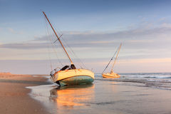 Beached Shipwrecked Boats on a Beach Cape Hatteras North Carolina. Two shipwrecked sailing boats beached on the coast of the Atlantic Ocean on the Cape Hatteras royalty free stock photos