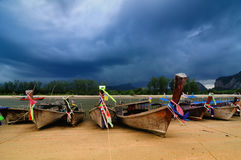 Boats on beach with stormy cloudscape Stock Image
