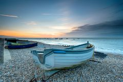 Sunrise at Selsey. Boats on the beach at sunrise at Selsey in West Sussex Stock Photos