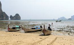 Boats Beached in Thailand. Three small boats beached on Tonsi Beach shoreline in Thailand Stock Photo