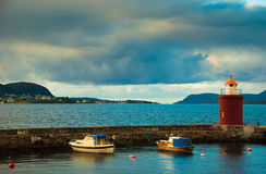 Boats and beacon in harbor. Alesund, Norway Royalty Free Stock Photography