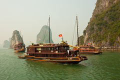 Boats in Beautiful Halong Bay. HALONG BAY, VIETNAM - NOVEMBER 30: Tourist junks navigating through the karst islands in Halong Bay. This is one of Vietnam's Stock Photo