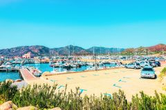 Boats at Beautiful Marina of Villasimius and the Bay of the Blue Waters of the Mediterranean Sea on Sardinia Island in Italy in. Summer. Cagliari region royalty free stock images
