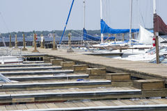 Boats And Boat Slips At A Lake. Boats in their slips on a long pier at a lake Royalty Free Stock Photos
