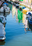 Boats in Burano Canal with Colorful Homes Reflected Stock Images