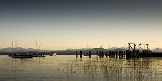Boats On a Calm Lake at Dawn. Boats sit on a calm lake in the early morning with mountains in the far distance. Horizontal shot Royalty Free Stock Photo