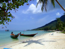 Boats on the calm ocean water, Thailand. Tourist boats on the shore of a white beach in Koh Phangan, Thailand Royalty Free Stock Photos