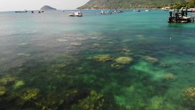 Boats in calm sea in port. Drone view of fishing and dive boats floating on tranquil surface of blue sea in harbor of stock video footage
