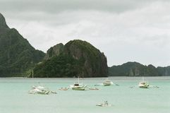 Boats on calm water. Yacht and outrigger boats that are anchored on the calm water, photos taken in El nido, philippines Stock Photography