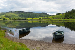 Boats calm water Watendlath Tarn Lake District Cumbria England UK. Watendlath Tarn Lake District Cumbria England with trees and mountains between the Borrowdale Stock Image