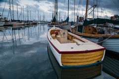 Boats on calm waters of marina. Small wooden motor boat anchored among many other boats on calm waters of Port Townsend marina as night falls in Washington state Royalty Free Stock Photography