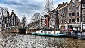 Boats in the canal in Amsterdam. Boats docked in the canal in Amsterdam with the town behind them royalty free stock photo