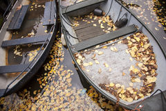 Boats in canal full of fallen autumn leafs Stock Images