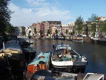 Boats in canal gracht, AMSTERDAM, NETHERLANDS. Boats in canal gracht ready to cruise and houses in the morning in warm and sunny summer day: AMSTERDAM Royalty Free Stock Images