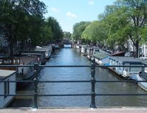 Boats in canal gracht ready to cruise in Amsterdam. Boats in canal gracht ready to cruise and traditional houses in the morning with clear blue sky in 2015 warm Royalty Free Stock Photo