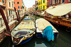 Boats on canal in Venice. Covered boats on water canal in Venice surrouded with colourful houses Royalty Free Stock Images