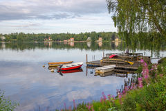 Boats, canoes and wild flowers. Wooden pier with boats and canoes on a Swedish lake with houses on the opposite shore Stock Photos