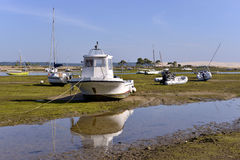 Boats at  Cap-Ferret in France. Boats at low tide at Cap-Ferret and Dune of Pilat in the background, ostreicole commune located on shore of Arcachon Bay, in the Stock Photos