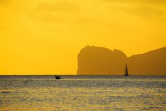Boats by the cape at sunset Stock Photos