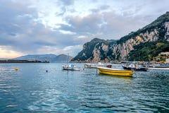 Boats in Capri island main harbor under cloudy skies. Capri, Italy Stock Photo