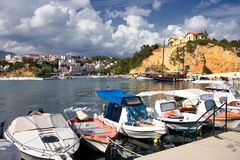 Boats and castle in a port in Greece Royalty Free Stock Photos