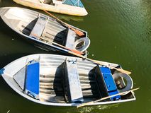 Boats and catamarans on a pond lake in a river canal with green flowered water are moored on the shore royalty free stock photos