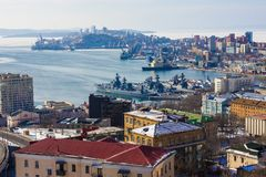Modern seaport. At the boats in the city port are military ships. Base of the Navy, Vladivostok. There are many modern and old buildings on the shore. Top view Stock Image