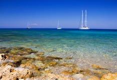 Boats. Clear sea and sailboats moored near the rocky coast Stock Photo