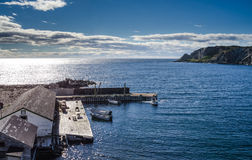 Boats at a cliffside dockhouse in Twillingate, Newfoundland. Royalty Free Stock Images