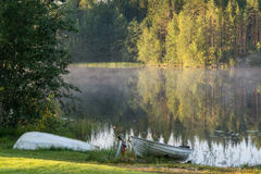 Boats on the coast of finnish lake at early morning. Royalty Free Stock Photos
