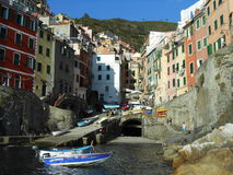 BOATS AND COLORFUL FACADES IN RIOMAGGIORE, ITALY Royalty Free Stock Photo