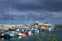 Boats in Corralejo harbor harbour with dark sky Royalty Free Stock Images