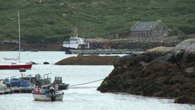 Boats in Cove Next To Stone Buildings. Steady, medium wide shot of boats in a cove next to a stone buildings stock video footage
