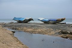 Boats waiting for fairer weather in Varkala, India Stock Photos