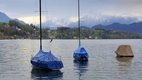 Boats covered with tarpaulin on lake Lucerne on a cloudy spring day. Town of Luzern, Switzerland. Boats covered with tarpaulin on lake Lucerne on a cloudy Royalty Free Stock Photography