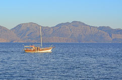 Boats in Crete Island. Boat in agios nikolaos port, Crete Island, Greece, with blue sky and mountain background Stock Photography