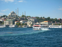 Boats crossiog Bosphorus in the city of Istanbul, Turkey and a mosque with high minarets on the background. Big beautiful muslim mosque made of gray stone with royalty free stock images