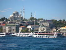 Boats crossiog Bosphorus in the city of Istanbul, Turkey and a mosque with high minarets on the background Stock Photo