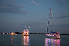 Power and Sailboats Participate in a Holida Boat Parade Royalty Free Stock Photo
