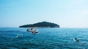 Boats cruising before island at Adriatic sea royalty free stock images