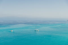 Boats on the crystal clear sea near the town of Tropea region Calabria - Italy Royalty Free Stock Photos