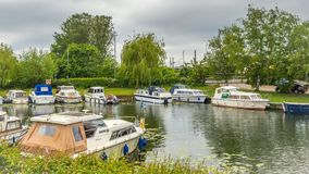 Boats of differing types and sizes line the banks of the River Great Ouse in Ely. Ely, Cambridgeshire, England - May 29, 2016: Boats of differing types and sizes stock images