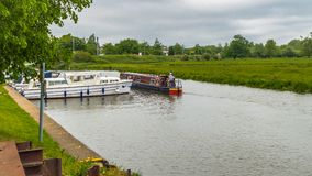 Boats of differing types and sizes line the banks of the River Great Ouse in Ely. Ely, Cambridgeshire, England - May 29, 2016: Boats of differing types and sizes Stock Photos