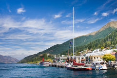 Boats dock to the pier on a lake. Sunny day at the Queenstown pier. South Island, New Zealand stock images