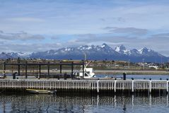 Boats at a dock in Ushuaia Harbor. Boats at a wooden pier in Ushuaia Harbor, Argentina, with snow covered mountains in the background Stock Photos