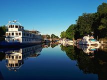 Boats Docked At Bobcaygeon, Ontario In Early Morning. Boats parked along the Bobcaygeon River in Bobcaygeon, Ontario, Canada, waiting for the locks to open along stock photos