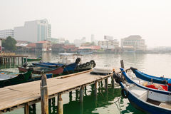 Boats Docked at Chew Jetty in Georgetown, Penang, Malaysia. Several boats, moored to a dock at Chew Jetty. Big buildings in the background Royalty Free Stock Photos