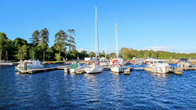 Boats docked on Lake Derg, Ireland. Here there is a group of boats docked on Lough Derg, county Clare, Ireland on a lovely clear blue sky evening Royalty Free Stock Images