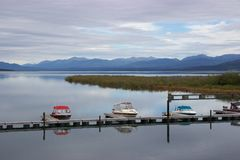 Boats docked in quiet mountain lake, Yukon, Canada. On a calm, cloudy day, a row of boats along a dock are reflected in the still waters of a lake, with the Stock Photo